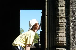 Boy peering inside a temple at Angkor Wat