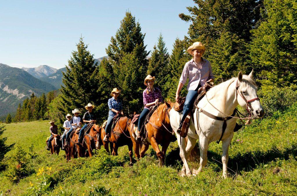 Dude Ranchers on horseback riding trail ride.