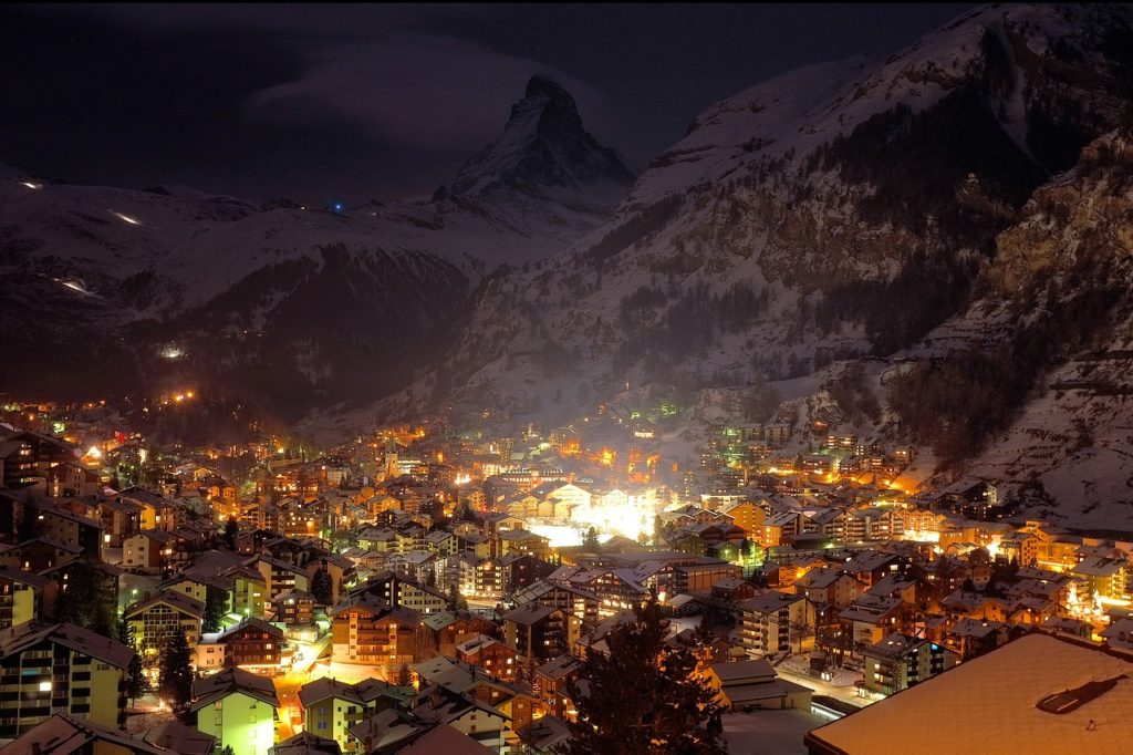 Mountain town illuminated after dusk.