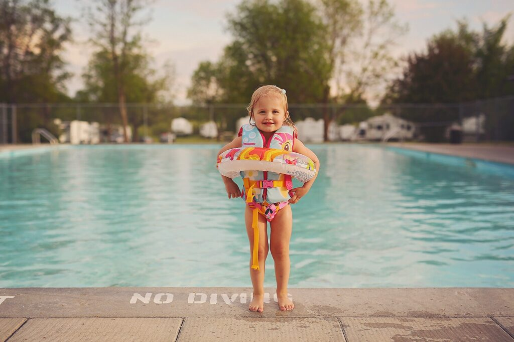 Young girl stands by pool