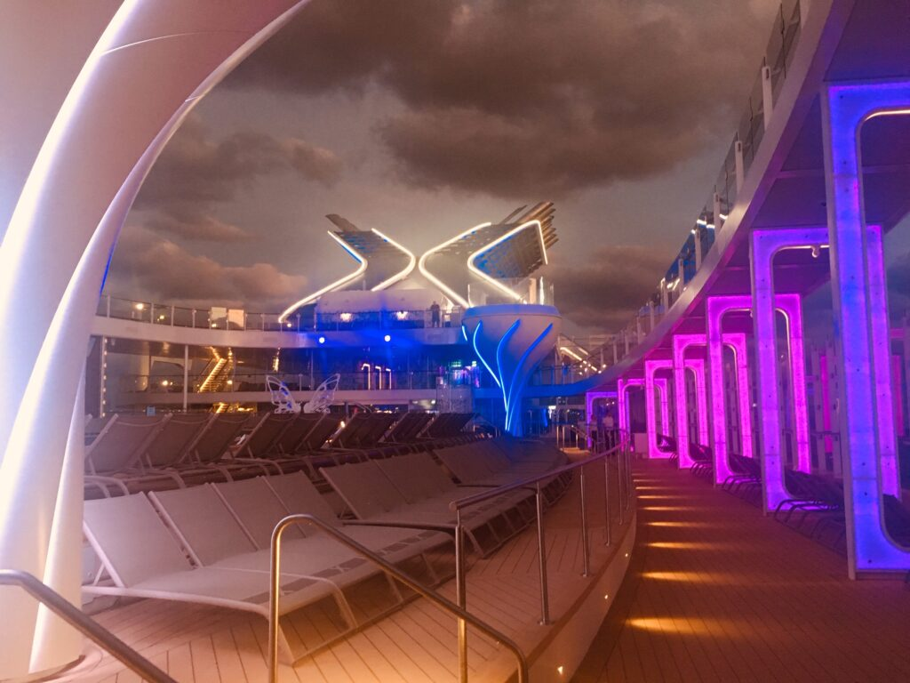 The Celebrity Edge cruise ship lights up at night.