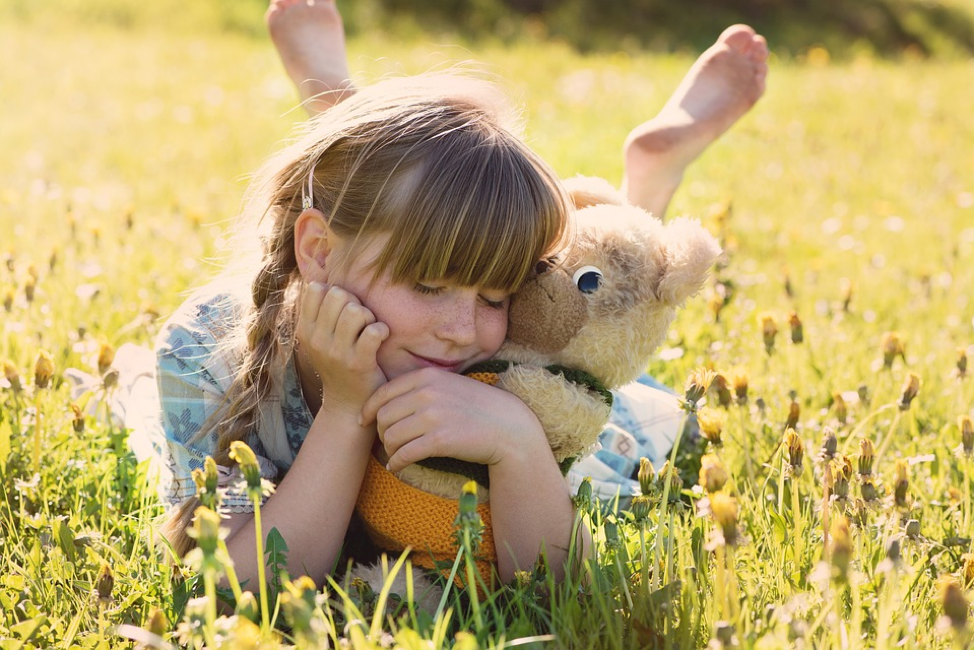 girl with stuffed toy in field