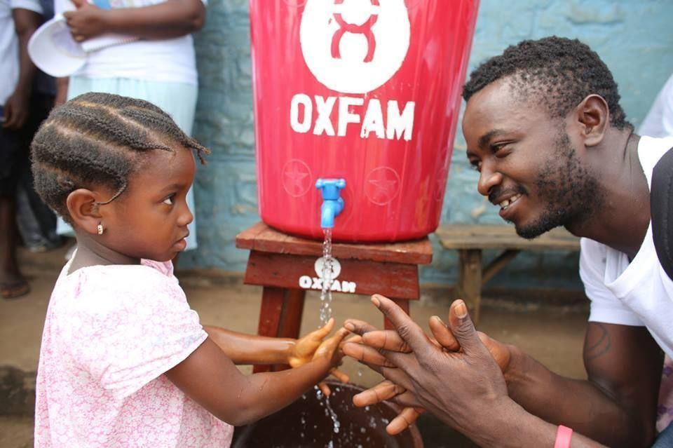 Oxfam aid worker supplies water to child