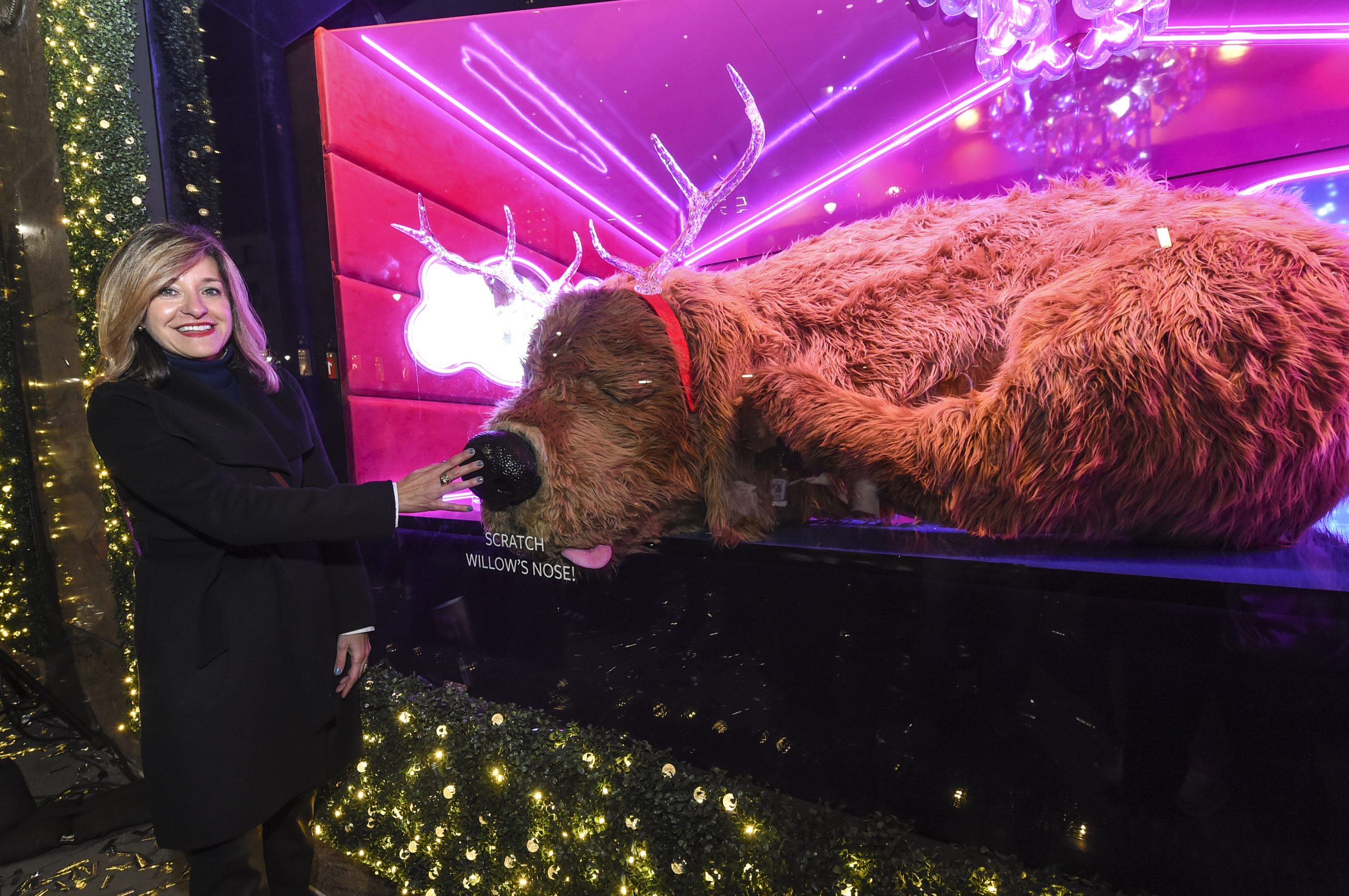 Woman patting animatronic dog at Macy's holiday windows.
