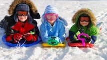 three kids sledding in snow