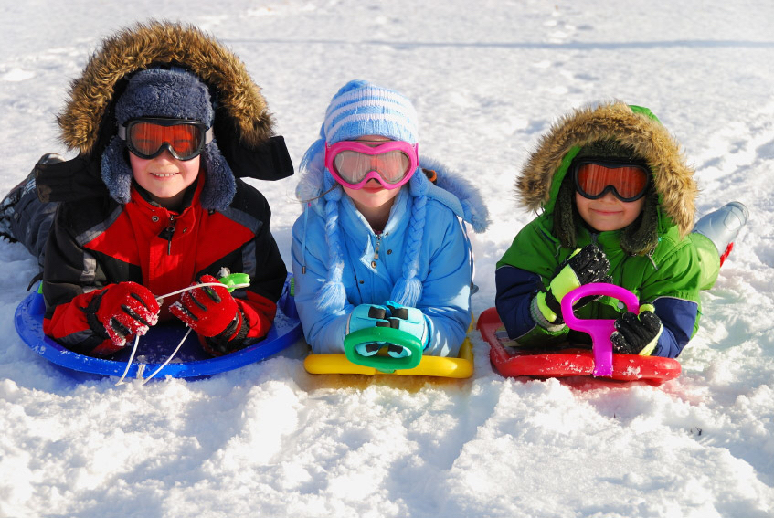 three kids with sleds in the snow.