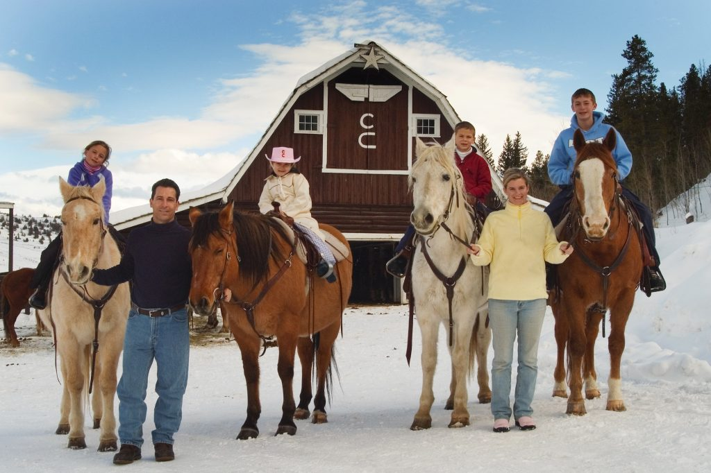 Family outside barn at C Lazy U Ranch in winter