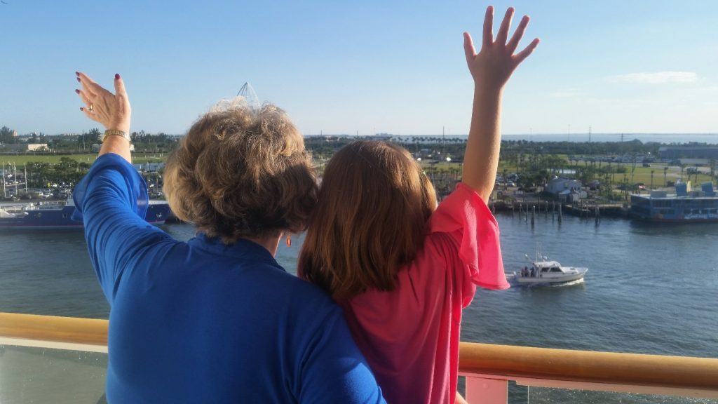 Grandmother and grandchild wave goodbye to shore from cruise ship deck.