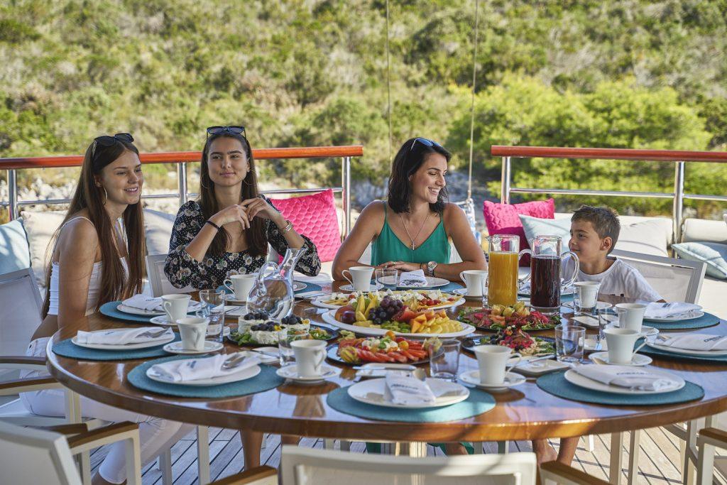 Family having breakfast on the yacht Corsario