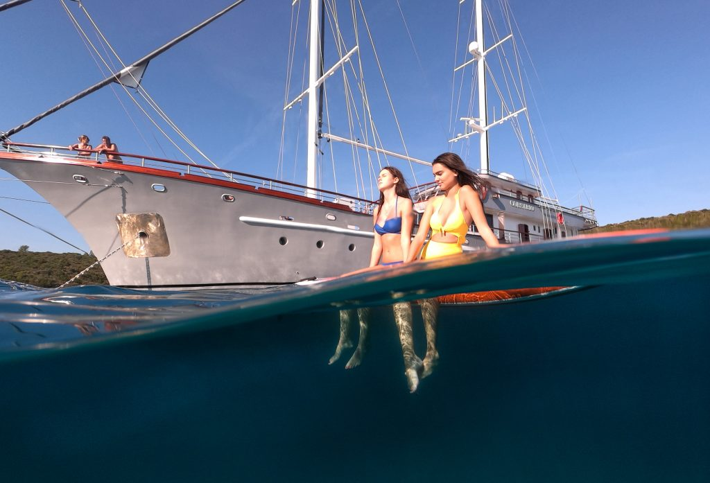 Girls sunbathe on paddleboard in one of the best places to sail in Croatia in the Adriatic.