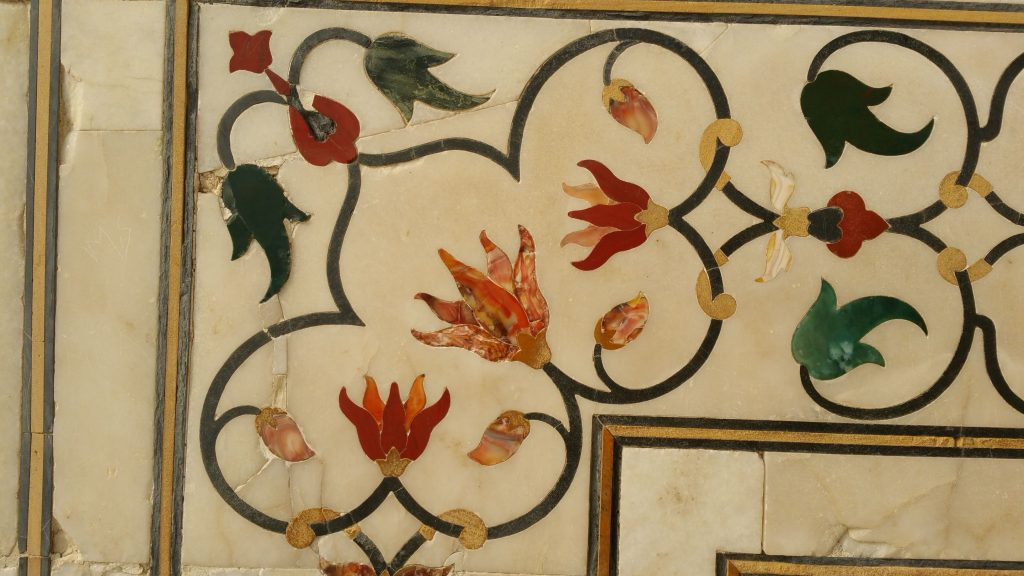 Close up of Taj Mahal wall with flowers made from agate, carnelian and jade inlaid in marble.