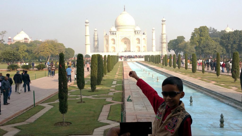 Young boy poses in front of the Taj Mahal.
