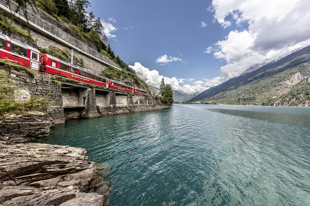 Bernina Express sightseeing train runs past scenic Lake Poschiavo in Switzerland.