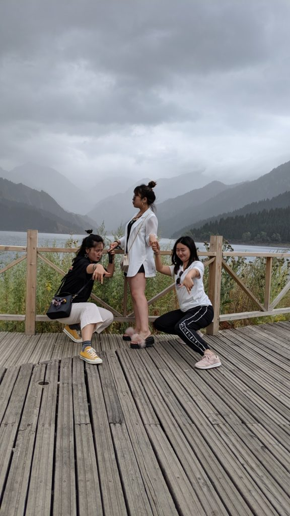 Chinese influencers posing in front of Heavenly Lake and Tian Shan.