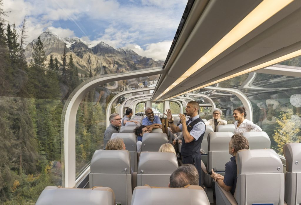 Rocky Mountaineer host describes Canadian wilderness in Gold Leaf class train car.