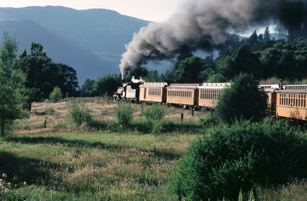 steam train and wooden rail cars travel through countryside