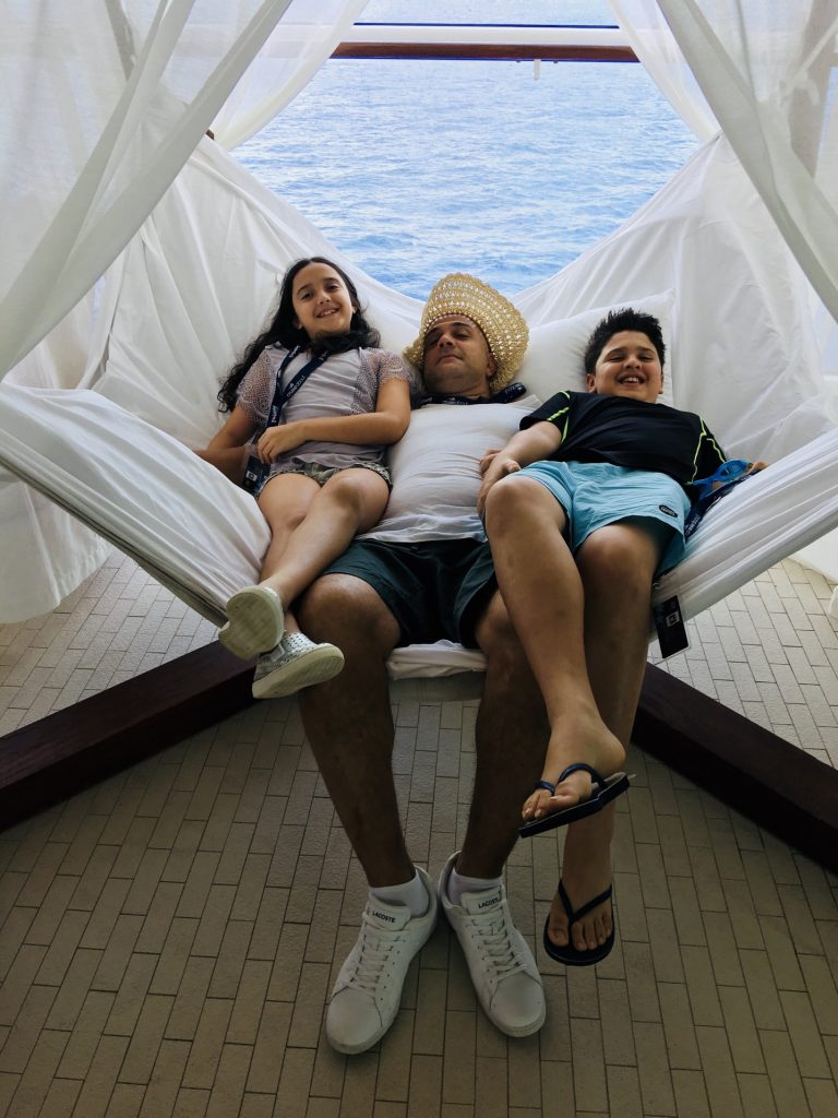 Dad and kids relaxing on hammock on deck of cruise ship.