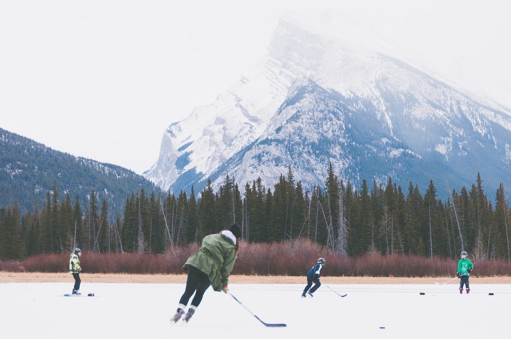 Playing hockey outside on a frozen lake.