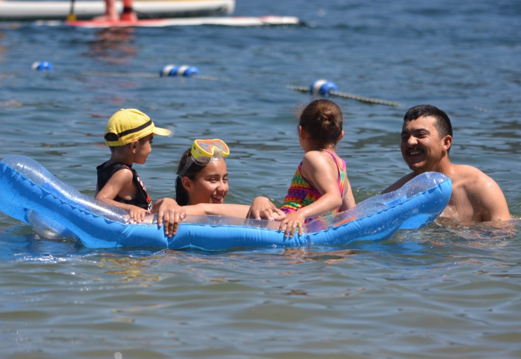 Family on raft playing in a lake.