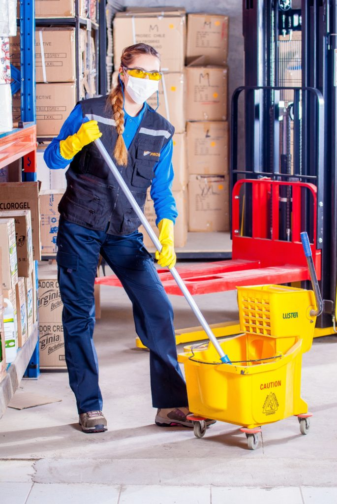 Woman in mask and gloves mopping floor.