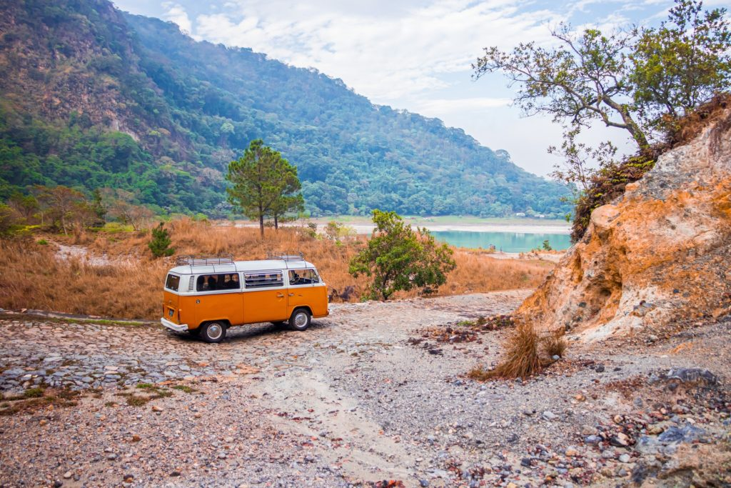 Volkswagen bus parked on unpaved trail near lake.