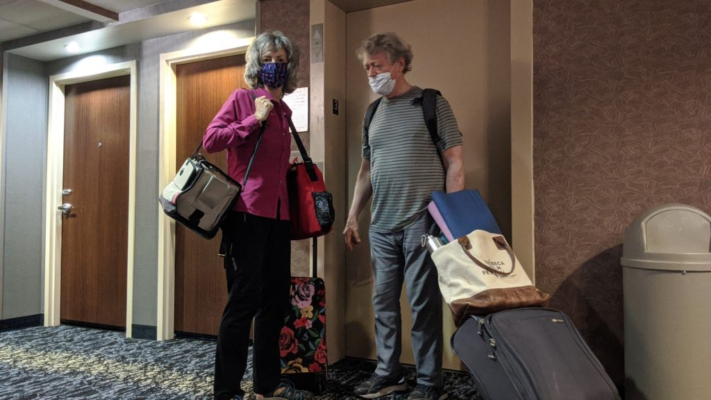 Couple in face masks at hotel elevator