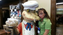 Woman poses with Alligator statue in Gift shop along the Boudin Trail of Southwest Louisiana.