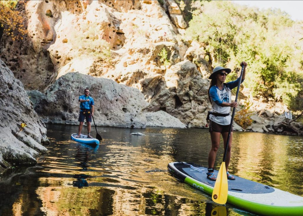 Two standup paddleboarders on a scenic river.