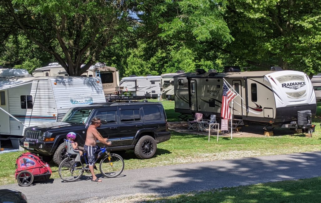 RVs in campground with kids on bikes.
