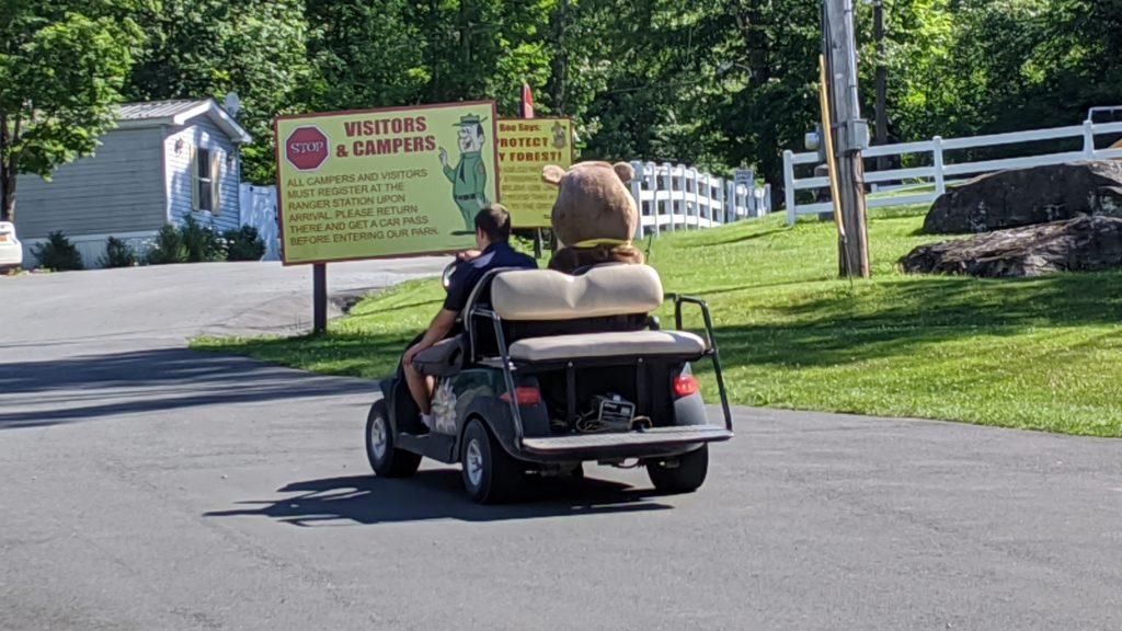 golf cart drives Boo-Boo Bear around the Jellystone Park at Birchwood Acres Resort