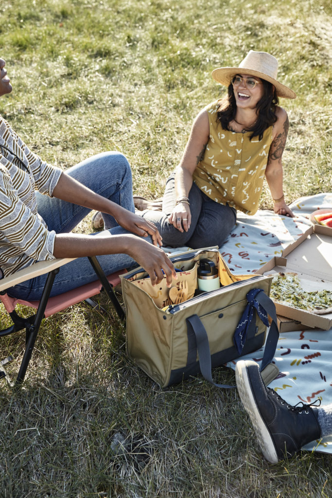 Two women haivng a pizza picnic on the grass.