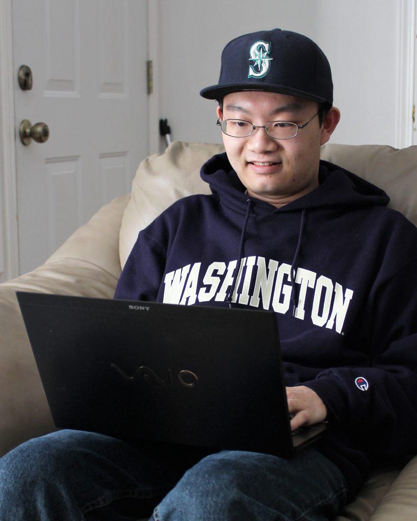 Student in Washington sweatshirt searching on computer
