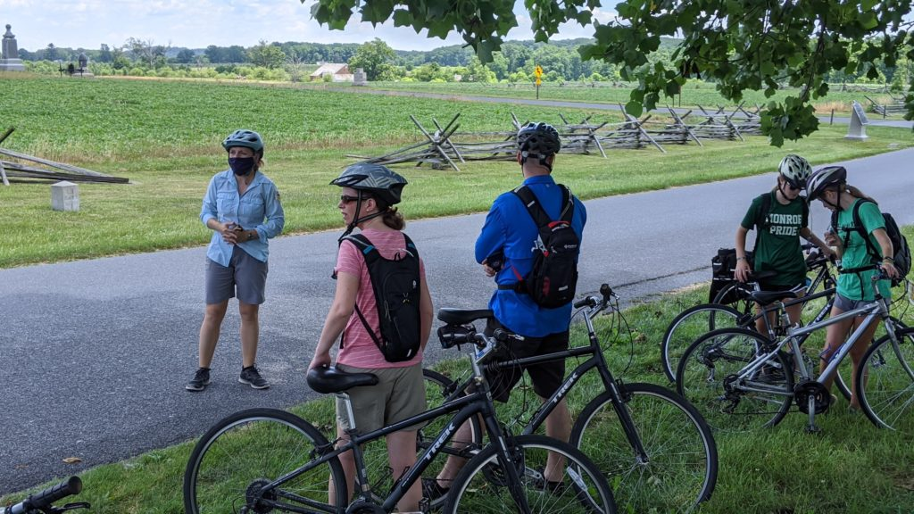 Guide Jessie and GettysBike Tour stops to talk about a battlefield at Gettysburg.