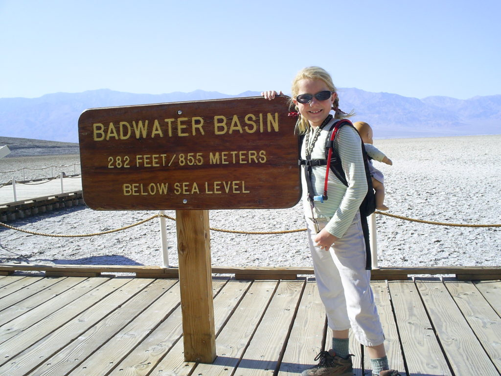 Girl at entry sign at Badwater, Death Valley National Park