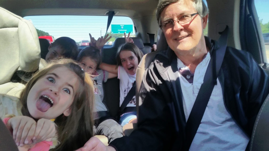 Kids making funny faces while grandpa drives the car on a fall road trip.