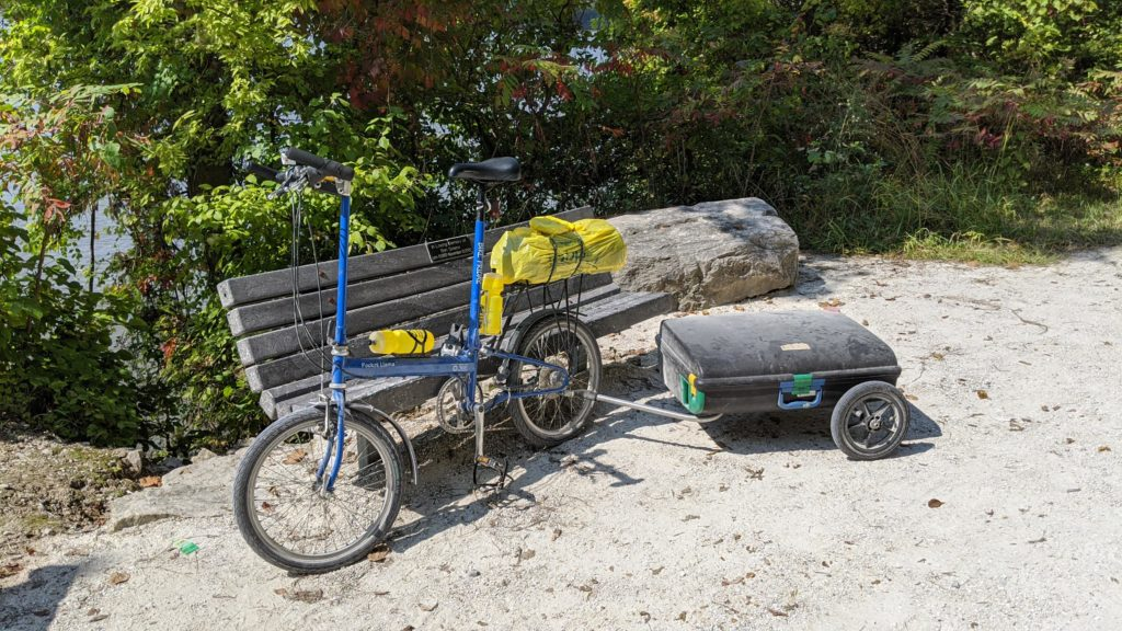 This bike folds up into that storage case, which holds a tent and camping gear!