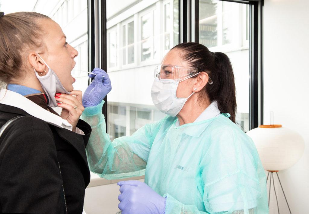 Swissair flight attendant gets COVID-19 antigen rapid test at airport.