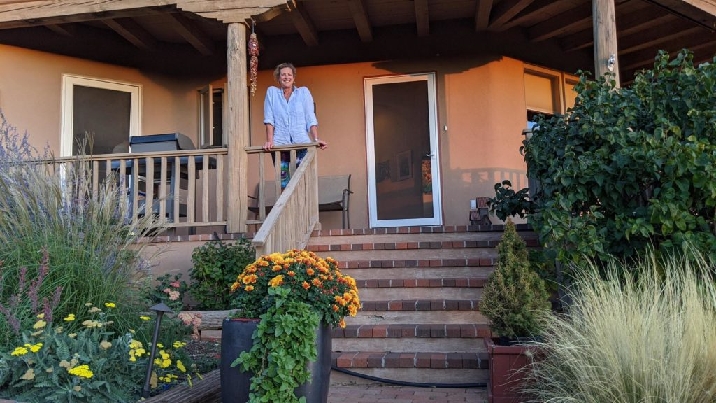 Jackie smiling from her Santa Fe porch.