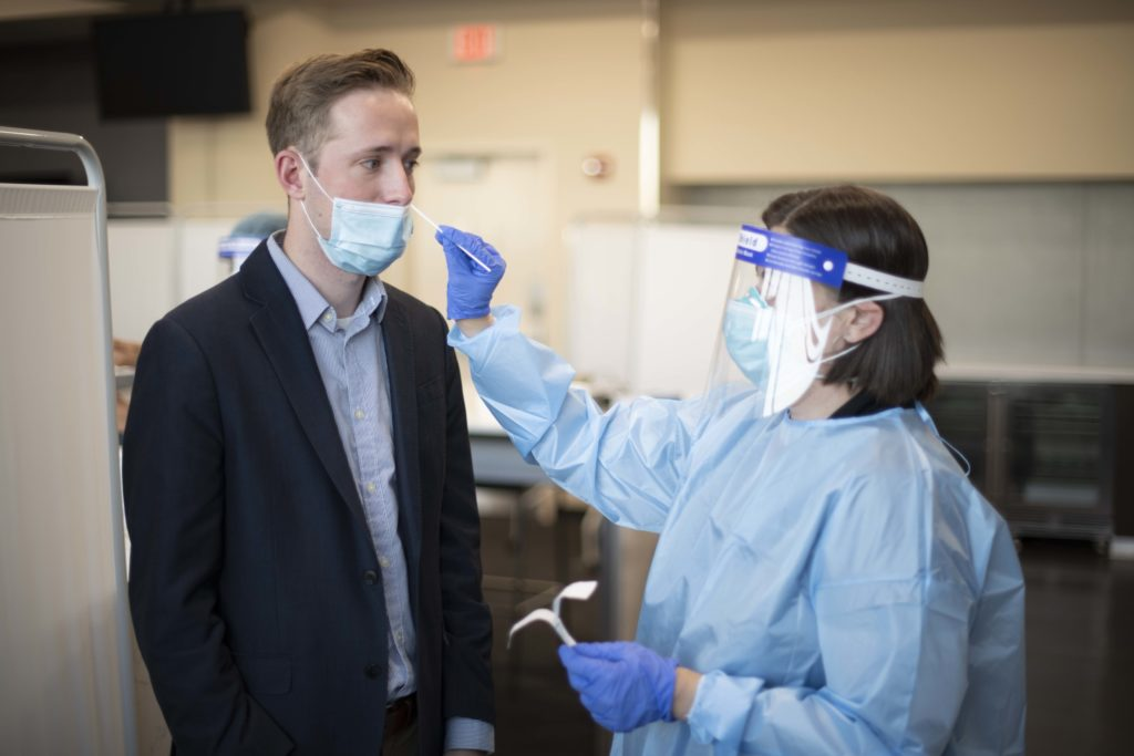 Man in suit gets COVID-19 nasal swab test.