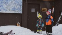 Kids wait in snow gear outside Alta Lodge Utah.
