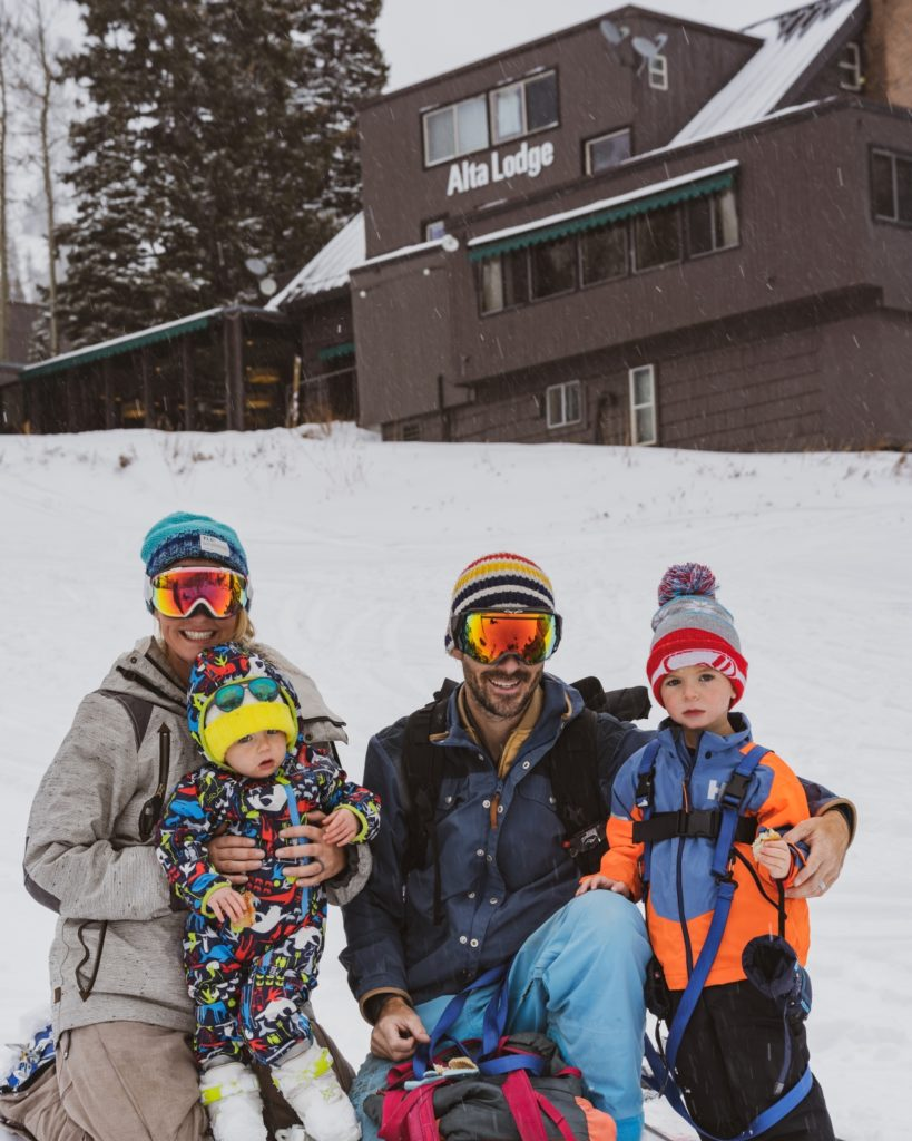 Family in snow gear outside Alta Lodge, Utah