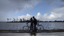 Two bike riders rest on the Mission Bay Bike Trail in the rain
