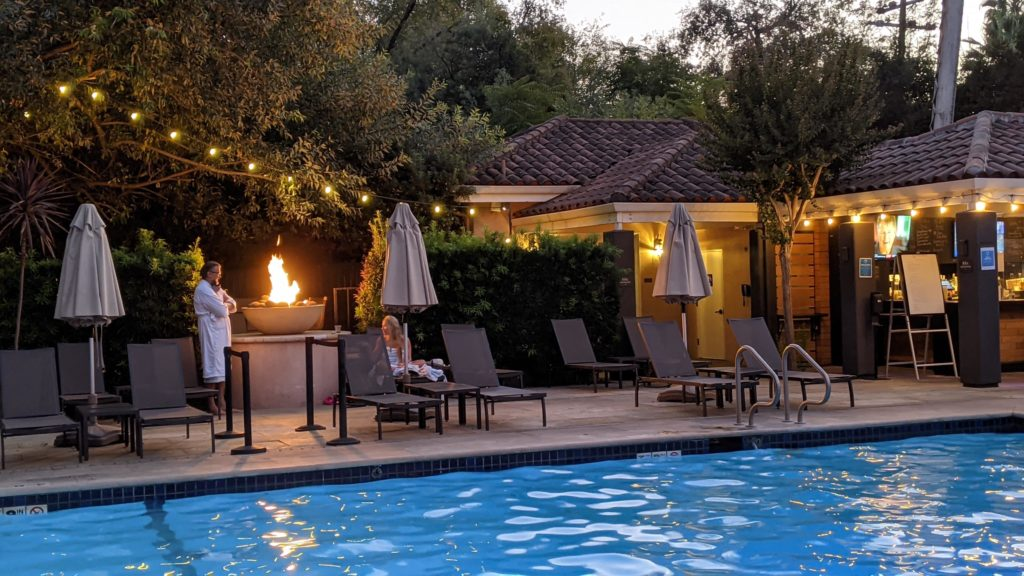 People in bathrobes by the fire pits at Fiarmont Sonoma Mission Inn mineral water pool.