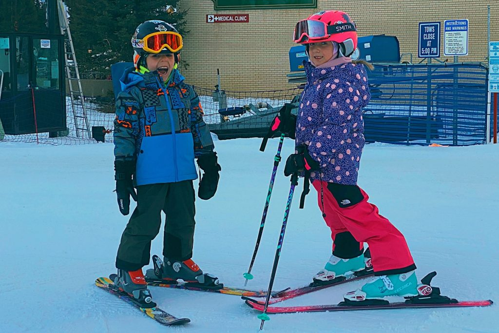 Two kids in ski gear standing in the snow at Alta, Utah.