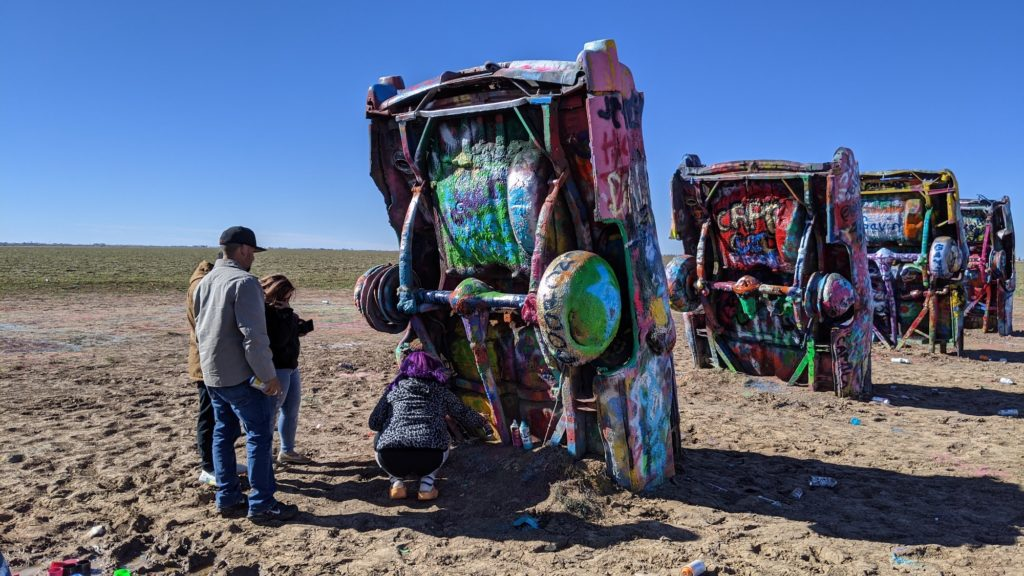 Visitors adding graffiti to Cadillac Ranch artwork in Amarillo, Texas.