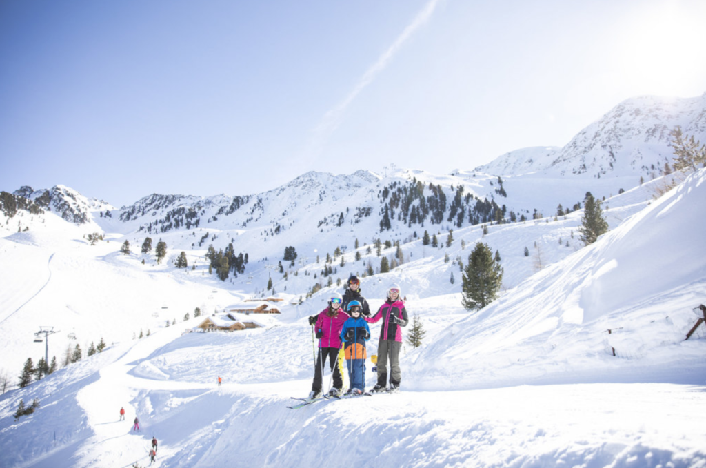 Family of four standing on snowy ski slope in Hochoetz, Tyrol region of Austria.
