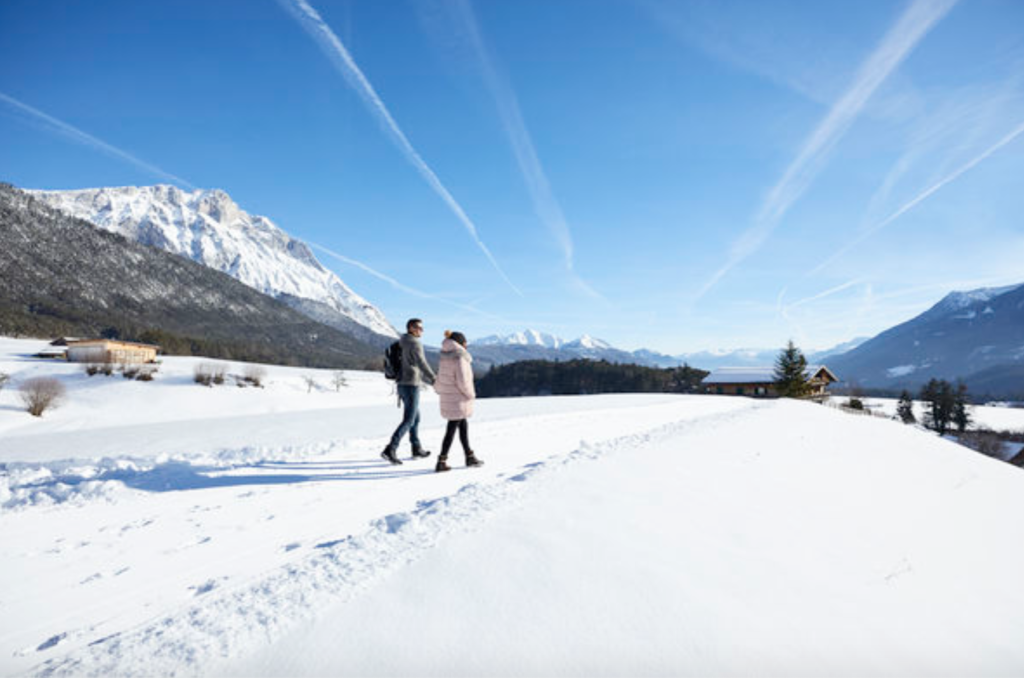 Young couple hiking in the snow outside Innsbruck, Austria with Alps in background.