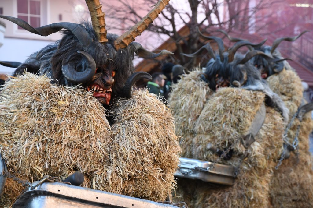 Scary Krampus figures in hay costumes parade through a Tyrol town in Austria.