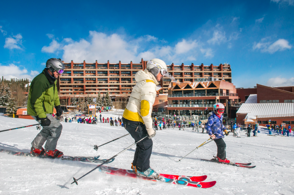 Parents taking child out on skis outside Beaver Run Resort in Breckenridge, Colorado.