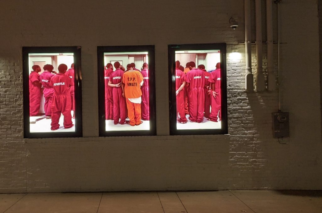 Video walls of incarcerated Black men outside the EEJI: Legacy Museum in Montgomery, Alabama.